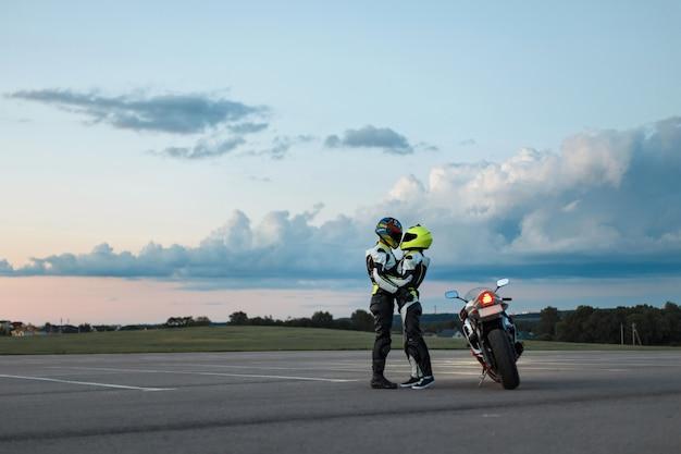 Молодая пара в байкерских костюмах возле мотоцикла.