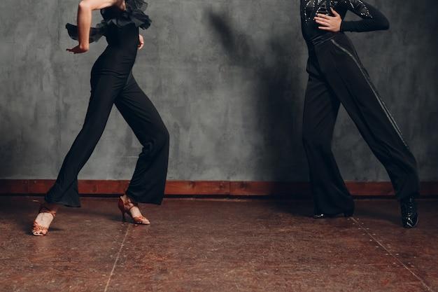 社交ダンス chachacha で踊る黒いドレスの若いカップル