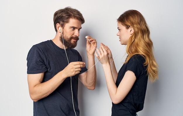 音楽技術のライフスタイルを聞いているヘッドフォンと黒のtシャツを着た若いカップル。高品質の写真