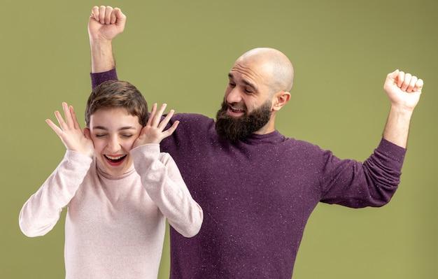 캐주얼 옷에 젊은 부부 수염 남자와 짧은 머리를 가진 여자 행복하고 흥분 녹색 벽 위에 서있는 발렌타인 데이 축하
