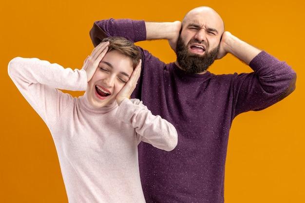 캐주얼 옷에 젊은 부부 수염 남자와 짧은 머리를 가진 여자 행복하고 오렌지 배경 위에 서 머리 발렌타인 데이 개념에 손을 잡고 흥분
