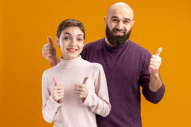 캐주얼 옷에 젊은 부부 수염 남자와 짧은 머리를 가진 여자 카메라 행복하고 쾌활한 미소 보여주는 오렌지 벽 위에 서있는 발렌타인 데이 개념 엄지 손가락
