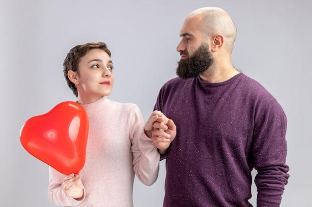 흰 벽 위에 서있는 발렌타인 데이를 축하하는 사랑에 행복한 심장 모양의 풍선을 들고 짧은 머리를 가진 그의 행복한 여자 친구를 찾고 캐주얼 옷 수염 난된 남자에 젊은 부부