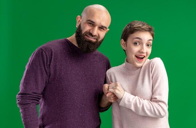 짧은 머리와 수염 난된 남자 캐주얼 옷에 젊은 부부는 녹색 배경 위에 유쾌하게 발렌타인 데이 개념 서 미소를 카메라를보고
