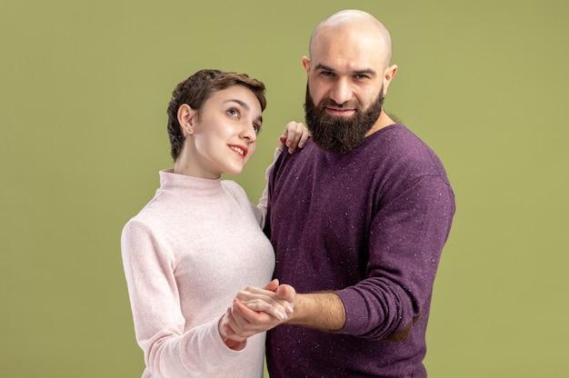 캐주얼 옷에 젊은 부부 행복 수염 남자와 짧은 머리를 가진 여자 사랑에 행복 함께 녹색 벽 위에 서있는 축하 발렌타인 데이 춤