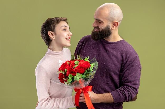 녹색 벽 위에 서있는 발렌타인 데이를 축하 그의 웃는 여자 친구에게 빨간 장미 꽃다발을주는 캐주얼 옷 행복 수염 난된 남자에 젊은 부부