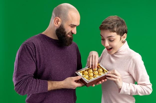 緑の背景の上に立っている彼の笑顔と驚きのガールフレンドバレンタインデーのコンセプトにチョコレート菓子を提供するカジュアルな服を着た若いカップル幸せなひげを生やした男