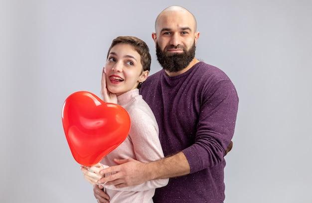 캐주얼 옷 남자와여자가 흰 벽 위에 서있는 발렌타인 데이를 유쾌하게 축하 lovesmiling에 행복 심장 모양의 풍선을 들고있는 젊은 부부