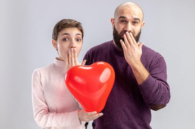 カジュアルな服装の若いカップルは、白い背景の上に立っているバレンタインデーを祝う手で口を覆って驚いて驚いたカメラを見てハート型の風船を持っている