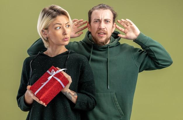 캐주얼 옷 남자와 여자에서 젊은 부부는 현재 찾고 혼란과 녹색 배경 위에 서있는 발렌타인 데이를 축하 불쾌