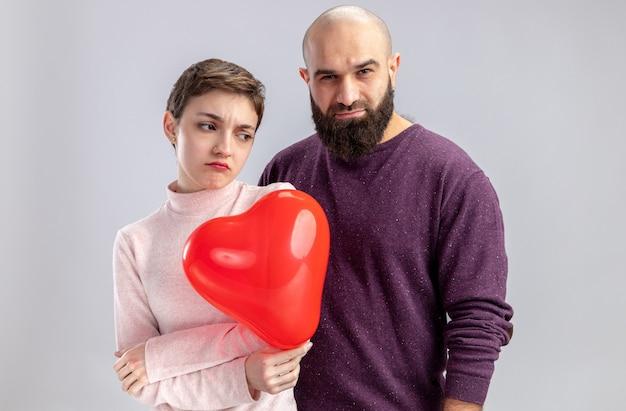 캐주얼 옷에 젊은 부부는 흰 벽 위에 서있는 발렌타인 데이를 축하하는 심장 모양의 풍선과 함께 짧은 머리를 가진 수염 난 남자와 여자를 불쾌하게