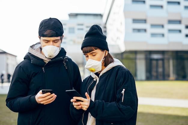 カジュアルな服を着た若いカップルが保護マスクを着用し、路上で携帯電話を使用し、ミレニアル世代が屋外で、スマートフォンで呼吸保護具をパンデミックしている