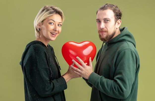 캐주얼 옷 여자와 남자가 심장 모양의 풍선을 함께 들고 젊은 부부는 녹색 벽 위에 서있는 유쾌하게 발렌타인 데이를 축하 웃고 사랑에 행복