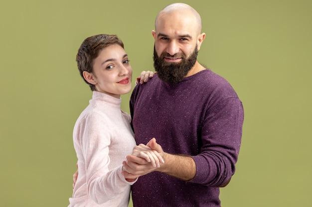 짧은 머리와 수염 난 남자 캐주얼 옷 여자에 젊은 부부는 녹색 벽 위에 서있는 발렌타인 데이를 축하 춤 사랑에 행복