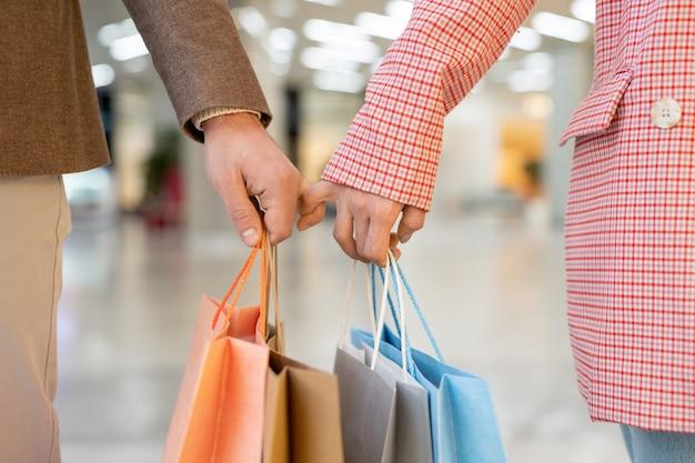 モールに沿って移動しながら紙袋を保持しているカジュアルウェアの若いカップル