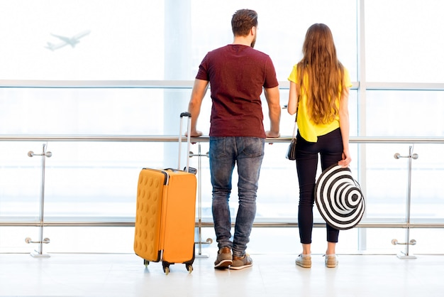 夏休み中に空港の出発エリアの窓の近くで荷物を持って待っているカラフルなtシャツを着た若いカップル