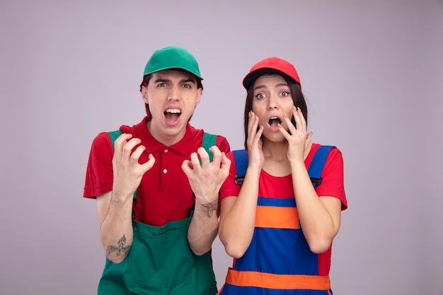 建設労働者の制服を着た若いカップルとキャップの怒っている男は、白い壁に隔離されたカメラを見て両方の顔の近くに手を保持している女の子に関係する空の手を示しています