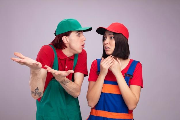 Молодая пара в униформе строителя и кепке невежественный парень показывает пустые руки, глядя на девушку, указывая в сторону с руками обеспокоенная девушка, держащая руки вместе, глядя на изолированную сторону