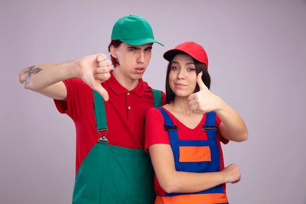 建設労働者の制服と帽子の眉をひそめている男の若いカップルは、白い壁に隔離された親指を下に見ている女の子を示しているカメラの男を見て喜んでいる女の子