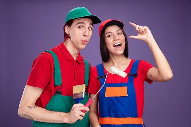 Молодая пара в форме и кепке строителя, смотрящая в камеру, удивила парня, держащего кисть и малярный валик, радостная девушка делает небольшой жест, изолированный на фиолетовой стене