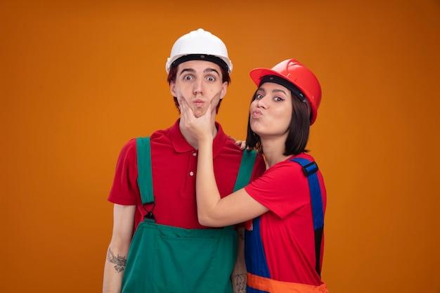 建設労働者の制服を着た若いカップルと、横顔に立っている安全ヘルメットの女の子が、無知な男の頬をつかんで唇をすぼめている