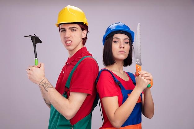 건설 노동자 유니폼과 안전 헬멧을 쓴 젊은 부부는 괭이 갈퀴를 들고 있는 공격적인 남자가 손을 잡고 흰 벽에 격리된 카메라를 보고 있는 것을 보았습니다.
