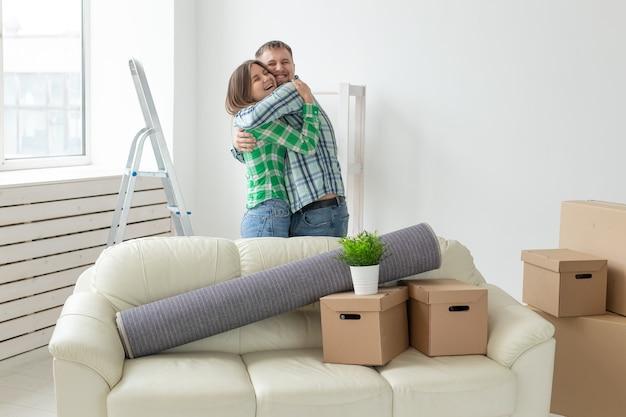 Молодая пара в джинсовых штанах радуется в своей новой квартире во время переезда. концепция