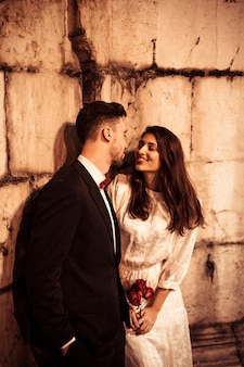 Young couple in elegantclothes leaning on wall