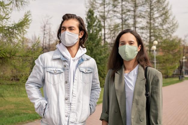 Молодая пара в масках гуляет вместе в городском парке во время эпидемии коронавируса
