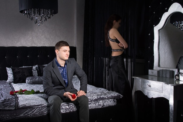 フォーマルな服装の若いカップル、寝室にとどまる、良い条件ではない