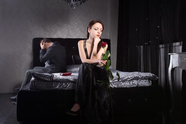 寝室で何かのために戦うフォーマルウェアの若いカップル