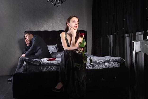 寝室に座っているときに関係の問題を抱えているフォーマルな服装の若いカップル。