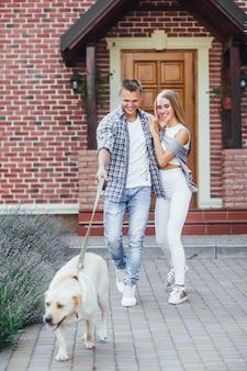 Молодая пара перед большим домом с красивым лабрадором.