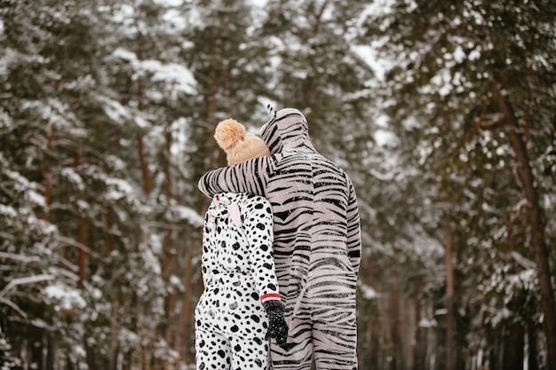 雪の森の背景に抱擁動物の面白い衣装の若いカップル。