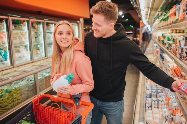 식료품가 게에서 젊은 부부. 음식을 사는 쾌활한 사람들. 그녀는 우유 병을 잡고 남자에게 미소를 짓습니다. 그녀는 트롤리를 가지고 다닙니다. 긍정적 인 좋은 커플.