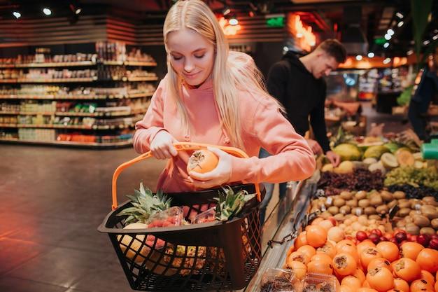 식료품가 게에서 젊은 부부. 좋은 여자는 식료품 바구니에 감을 넣고 아래를 내려다 보면서.