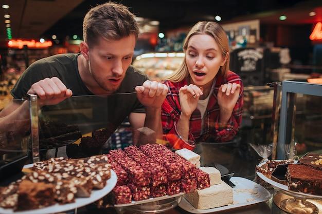 Молодая пара в продуктовом магазине, собирание сладостей