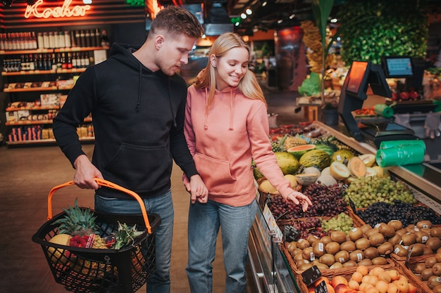 식료품가 게에서 젊은 부부. 그들은 과일을 함께 줍습니다. 선반에 열매의 이국적인 다른 종류.