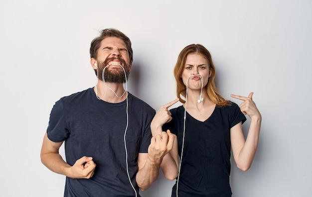 音楽の楽しい友情の感情を聞いているヘッドフォンで若いカップル