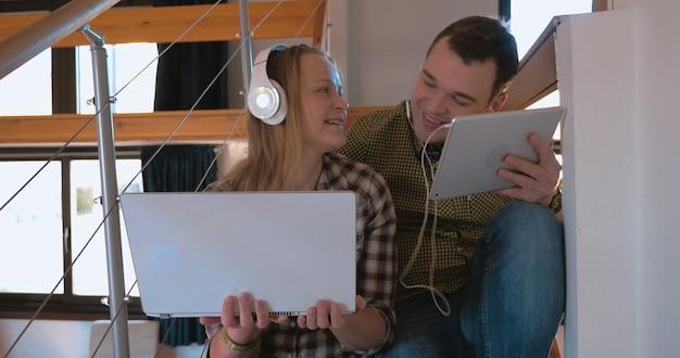 Молодая пара в наушниках дома, наслаждаясь музыкой
