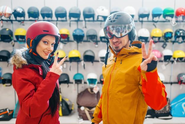 스키 또는 스노우 보드, 스포츠 샵 헬멧에 젊은 부부.
