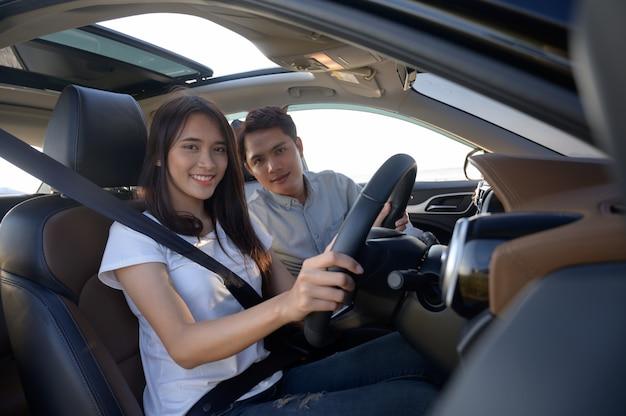 彼の車の中で若いカップル、田舎道を運転して満足しています。車の中で幸せな若い女性と若い男性