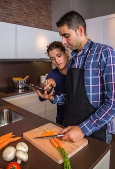 家庭の台所で食事を準備し、電子タブレットでレシピを探している若いカップル。現代の家族のライフスタイルの概念。