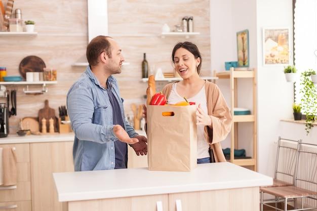 시장에서 식료품으로 가득 찬 종이 봉지를 들고 부엌에 있는 젊은 부부. 남성과 여성을 위한 건강한 행복한 관계 생활 방식, 함께 쇼핑 제품
