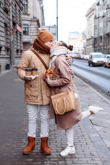 Young couple in love are kissing on the street in cold winter weather. They have coffee and some food.