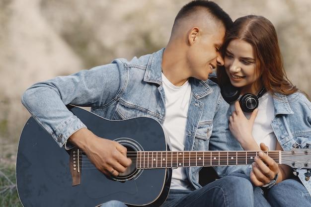 Молодая влюбленная пара, парень играет на гитаре