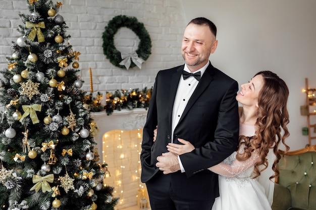 クリスマスの結婚式の日にクリスマスツリーで飾られた背景にスタジオでポーズをとる愛の花嫁と花婿の若いカップル。幸せと愛の瞬間をお楽しみください。