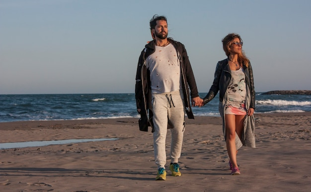 Молодая влюбленная пара на берегу моря во время заката