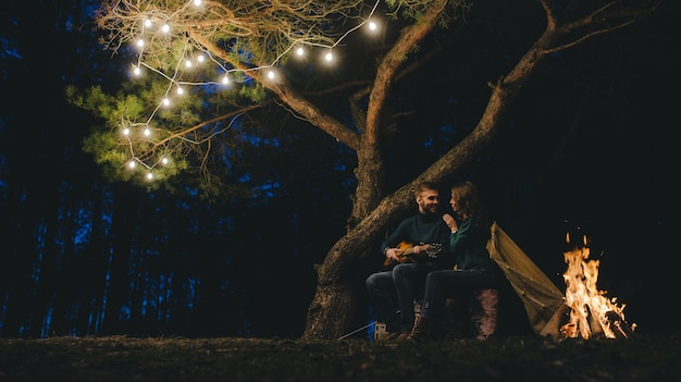 Молодая влюбленная пара туристов, отдыхающих в кемпинге, сидя у костра против палатки в лесу с ретро-гирляндой, фото с большим шумом, выборочный фокус