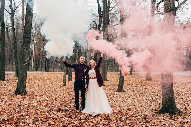Молодая влюбленная пара празднует свою маленькую свадьбу осенью и развлекается с дымовыми шашками
